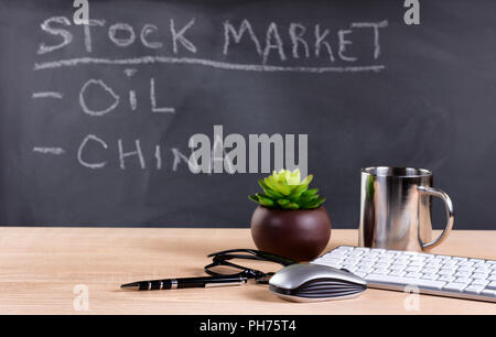 Studying the financial markets with blackboard in background - Stock Photo