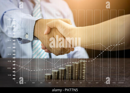 shaking hands with stacked of coins and finance graph - Stock Photo