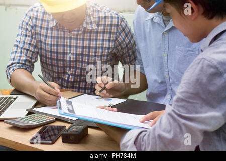 engineers and workers meeting and planning on construction site. - Stock Photo