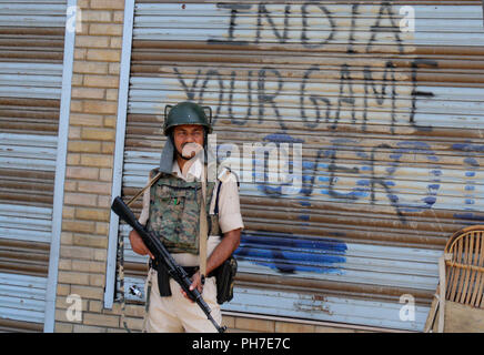Srinagar, Kashmir. 31st Aug 2018.  Indian paramilitary trooper stands guard next to the closed shops , during a second day of a strike called by Kashmiri separatists against attempts to revoke state constitution articles 35A and 370.Top Court Defers Hearing On Jammu And Kashmir's Article 35A To January Supreme Court today. The state government told the court that any hearing on the matter now will create law and order issues in the panchayat elections, which will be held in the next three months.©Sofi Suhail/Alamy Live News - Stock Photo