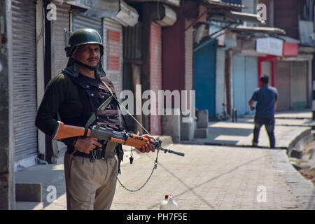 Srinagar, Kashmir. 31st Aug 2018. An Indian Policeman stands alert during restrictions in downtown area of Srinagar.Authorities imposed Restrictions in many parts of Srinagar Summer Capital Of Indian Kashmir on Friday to Prevent the protect called by Joint Resistance Leadership against proposed removal of Article 35-A in State. Kashmir valley observed Complete shutdown in favour to safeguard the Article 35A which grants special rights to the permanent residents. Credit: Idrees Abbas/SOPA Images/ZUMA Wire/Alamy Live News - Stock Photo
