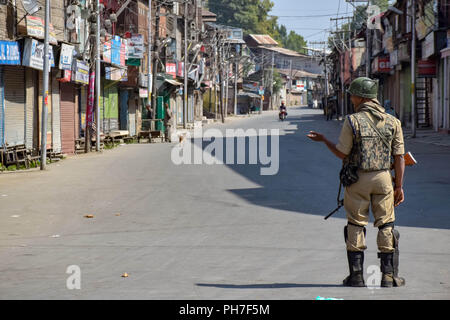 Srinagar, Kashmir. 31st Aug 2018. An Indian policeman stands alert on deserted streets of srinagar during restrictions.Authorities imposed Restrictions in many parts of Srinagar Summer Capital Of Indian Kashmir on Friday to Prevent the protect called by Joint Resistance Leadership against proposed removal of Article 35-A in State. Kashmir valley observed Complete shutdown in favour to safeguard the Article 35A which grants special rights to the permanent residents. Credit: Idrees Abbas/SOPA Images/ZUMA Wire/Alamy Live News - Stock Photo