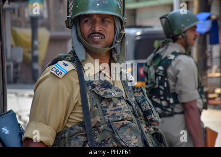 Srinagar, Kashmir. 31st Aug 2018. An Indian Policeman Stands Alert During restrictions in Srinagar.Authorities imposed Restrictions in many parts of Srinagar Summer Capital Of Indian Kashmir on Friday to Prevent the protect called by Joint Resistance Leadership against proposed removal of Article 35-A in State. Kashmir valley observed Complete shutdown in favour to safeguard the Article 35A which grants special rights to the permanent residents. Credit: Idrees Abbas/SOPA Images/ZUMA Wire/Alamy Live News - Stock Photo