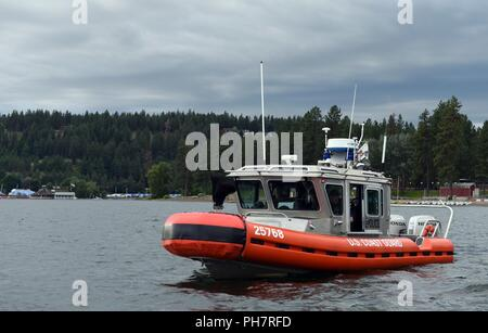 A Coast Guard crew aboard a 25-foot Response Boat-Small patrols the waters of Lake Coeur d'Alene in Idaho on June 30, 2018. This was the Seattle-based Coast Guard crew's first time on the lake and their efforts were part of an initiative to inform boaters of the dangers of boating under the influence of alcohol and to enforce laws concerning safe boating. - Stock Photo