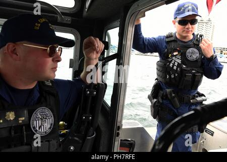 Coast Guard boat crewmembers from the Maritime Safety and Security Team in Seattle chat while patrolling the waters of Lake Coeur d'Alene in Idaho, June 30, 2018. Lake Coeur d'Alene is one of 61 navigable lakes in Idaho, six of which have federal jurisdiction. - Stock Photo