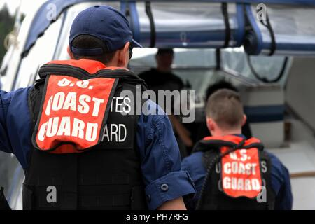 Two Coast Guardsmen, both stationed in Seattle, speak with a recreational boater on Lake Coeur d'Alene in Idaho, June 30, 2018. Coast Guard boat crews included members from Seattle's Sector Puget Sound Boarding Team and the Maritime Safety and Security Team. - Stock Photo