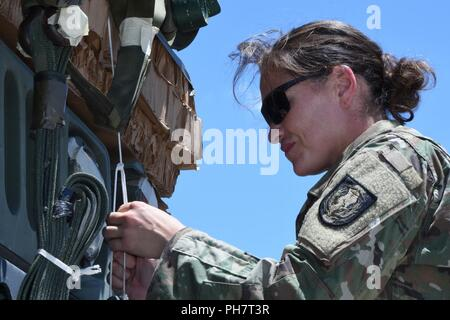 Texas Army National Guardsmen Staff Sergeant Jenny Spence, 294th Quartermaster Company platoon sergeant, secures pallet straps on the Humvee before it air drops from a Texas Air National Guard C-130 Hercules Wednesday, June 27, 2018, at Naval Air Station Fort Worth Joint Reserve Base, Texas. The Texas Military Department supported this joint training initiative with the Texas National Guard's 294th Quartermaster Company, Camp Mabry in Austin, and the 136th Airlift Wing, delivering the first fully successful Texas Humvee airdrop from a C-130 Hercules. - Stock Photo