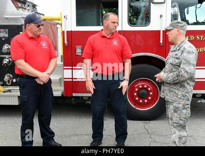Col. Roman Hund, installation commander, coins Keith Williams, left, and Vincent Sanchez, Hanscom fire fighters, outside the Fire Department at Hanscom Air Force Base, Mass., June 15. The commander coined them for training they provided last month to him. - Stock Photo