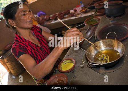 Horizontal portrait of a lady prepping traditional Sri Lankan food. - Stock Photo