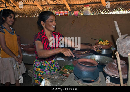 Horizontal portrait of a lady showing her daughter how to cook traditional Sri Lankan food. - Stock Photo
