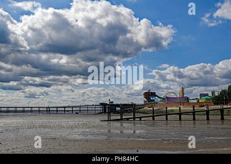 Capturing enormous white clouds gathering over amusements and beach at South End on sea, in Essex. - Stock Photo