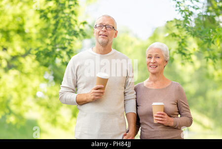 senior couple with coffee cups natural background - Stock Photo