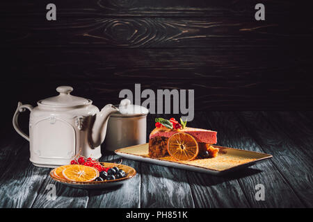 carrot cake with berry filling on plate, orange slices, blueberries and cranberries on saucer near teapot on wooden table - Stock Photo
