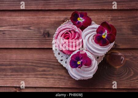Box with pink zephyr and flowers on grey wooden background - Stock Photo