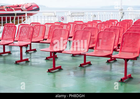 Rows of red seats empty on green ferry ship deck - Stock Photo