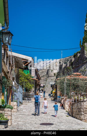 Stari Bar, Montenegro - April 2018 : Mother and children walking up the hilly street full of souvenir shops leading to the old fortress ruins - Stock Photo