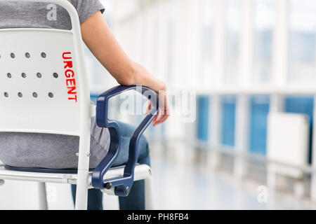Female patient, sitting in a wheelchair for patients feeling not well enough to stand, waiting to be taken care of in a modern hospital (shallow DOF;  - Stock Photo