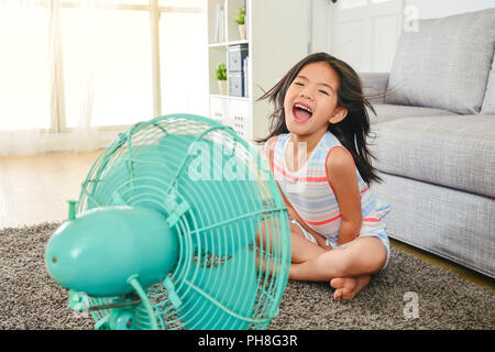 litle cute girl laughing and sitting in front of fan. refreshing herself from hot weather with legs crossed. - Stock Photo