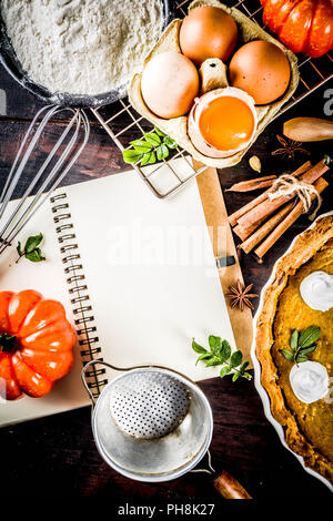 Autumn baking background, baking ingredients for pies, cookies - pumpkins, pumpkin pie, spices, flour, eggs, rolling pin, whisk, old wooden table top  - Stock Photo