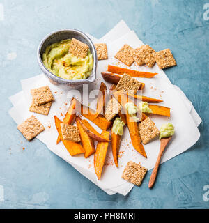 Avocado dip in bowl with spices and sweet potato on table. View from above. Clean eating diet concept - Stock Photo