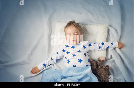 six years old child sleeping in bed with alarm clock - Stock Photo
