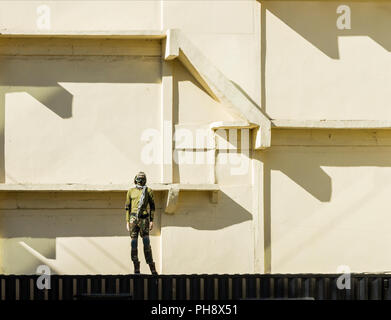 Soldier standing with on the wall background. - Stock Photo