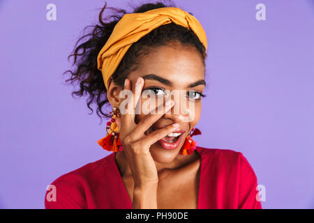 Close up portrait of a happy young african woman in headband over violet background, looking at camera with hand at her face - Stock Photo