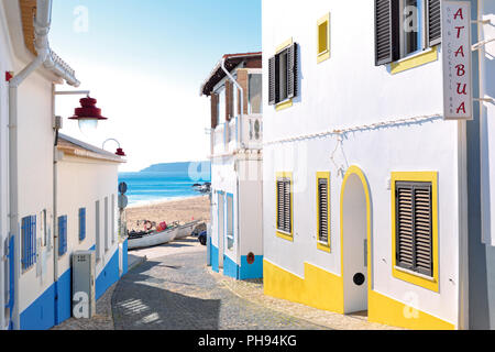 Romantic tiny alley with colorful houses leading to  a sandy beach with fishing boat and sea view - Stock Photo