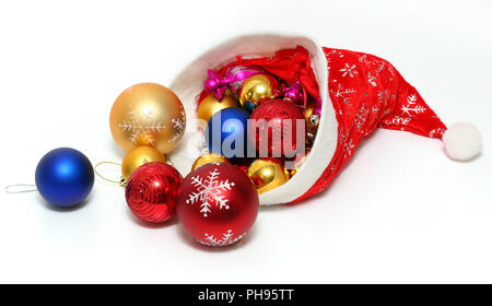 christmas balls, toys in red hat of Santa Claus - Stock Photo