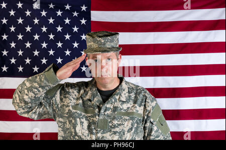 Male veteran solider saluting with USA flag in background - Stock Photo