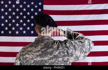 Veteran solider saluting the flag of USA flag - Stock Photo