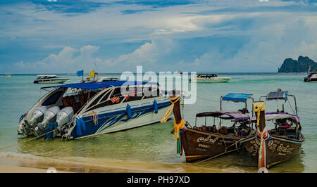 Traditional Thai Longtail boats vs speed boats - Stock Photo