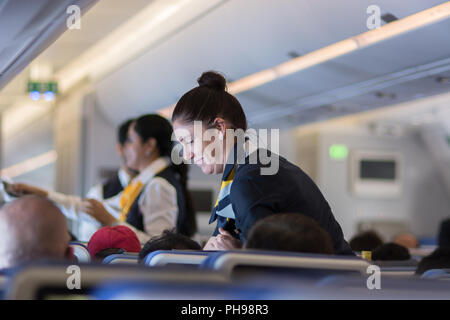 Mumbai, India - July 8, 2018 - Flight attendants speaking with a passenger sitting in the economy class of the route Munich - Mumbai of Lufthansa Airl - Stock Photo