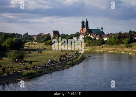 Young people during their rest on the Warta River in Poznań. Cathedral Island (Ostrow Tumski) in background. - Stock Photo