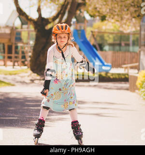 Young girl learning skating with inline skates - Stock Photo