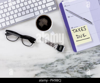 Marble desktop surface with calendar for tax reminder - Stock Photo
