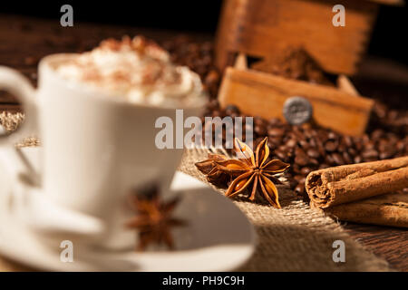 Close-up on star anise and cinnamon sticks with coffee cup - Stock Photo