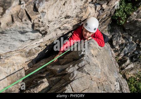 A young boy on a multi pitch rock climb in the Rhone valley, Switzerland - Stock Photo