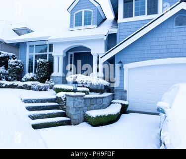 Snow covered sidewalk in front of home during winter snowfall - Stock Photo