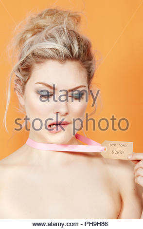 Young woman wearing price tag around her neck - Stock Photo