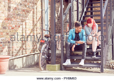 Teenage couple sitting on steps together - Stock Photo