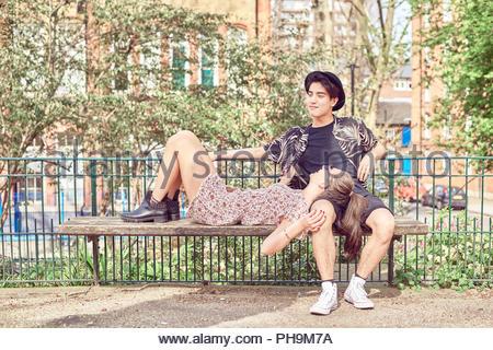 Teenage girl lying in boyfriend's lap at park - Stock Photo