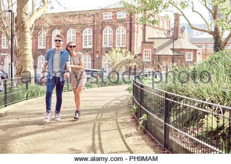 Teenage couple walking in park - Stock Photo