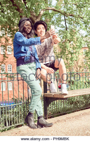 Teenage couple taking selfie in park together - Stock Photo