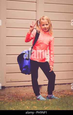 Young girl aged 5-7 showing victory sign - Stock Photo