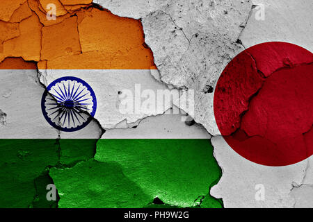 flags of India and Japan painted on cracked wall - Stock Photo