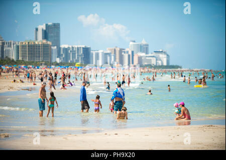 MIAMI - CIRCA AUGUST, 2018: Crowds of people enjoy the sea and sand of South Beach on a hot summer weekend. - Stock Photo