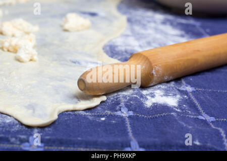 Homemade Phyllo or strudel dough with cheese and rolling pin - Stock Photo