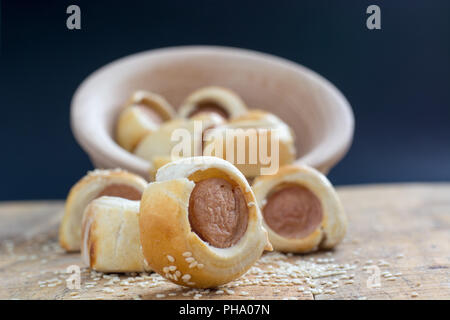 Sausages rolled in croissant dough baked cooling on metal rack. - Stock Photo