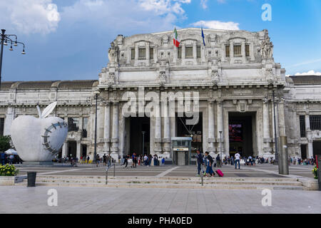 Milan Railway station facade with artwork of The Reintegraded Apple sculpture outside Milano Centrale at Piazza Duca dAosta, Milan, Lombardy, Italy - Stock Photo